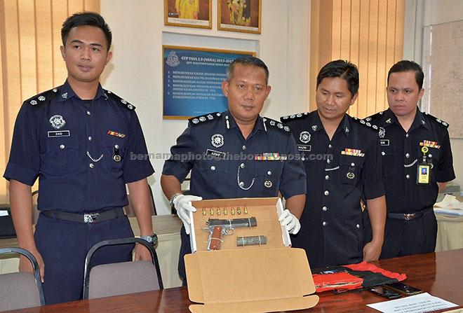 Azhar menunjukkan sepucuk pistol berserta tujuh butir peluru yang dirampas berikutan penahanan tiga lelaki di Jalan Buli Sim-Sim pada 3 April lepas ketika mengadakan sidang media di Sandakan, semalam. — Gambar Bernama