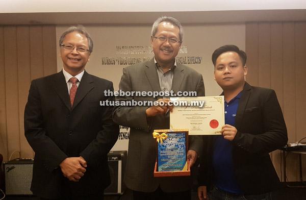 Osman (tengah) menyampaikan sijil peserta terbaik Kursus Video Production, Motion Graphics dan Special Effects kepada salah seorang peserta kursus iaitu Redzwan Yasun. — Gambar Jabatan Penerangan